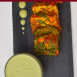 pin image of yogurt mint sauce in a small bowl with paneer tikka on black plate with text overlay on top and bottom.