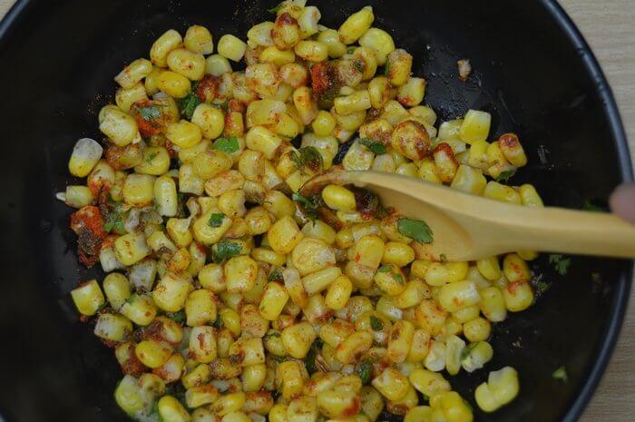 mixing masala corn with spoon.