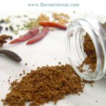 pin image with green text overlay on top showing dark coloured spice powder on a marble along with whole spices placed next to it.
