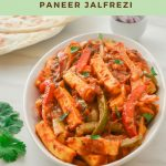 paneer jalfrezi in a white bowl with paratha and pinch bowl of onion slices placed behind and a text overlay on top and bottom.