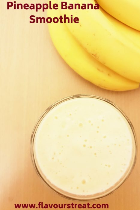 glass of pineapple smoothie and bananas on table