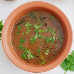 dal rasam in brown bowl placed on white table