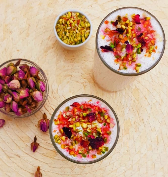 rose lassi in 2 glasses with dried rose buds and chopped pistachios in a bowls