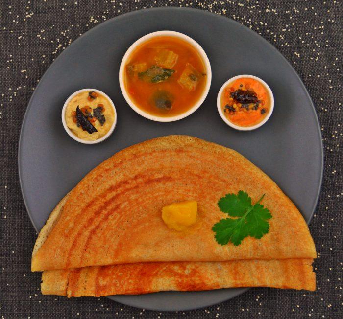 2 millet dosas sambar and 2 chutneys on black plate
