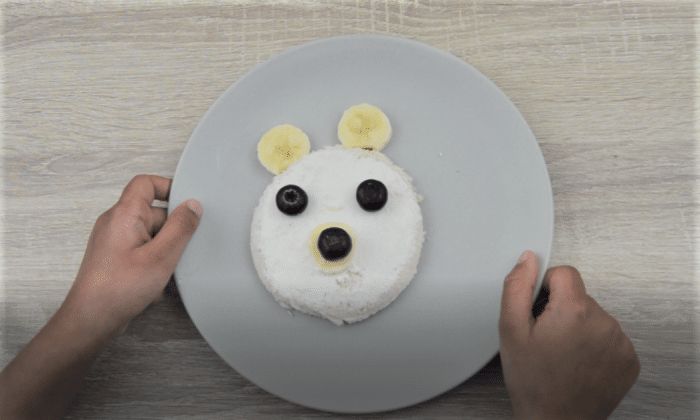 child holding plate having teddy face sandwich