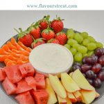 fruits arranged on a grey plate with a bowl of yogurt fruit dip in centre placed on a white table.