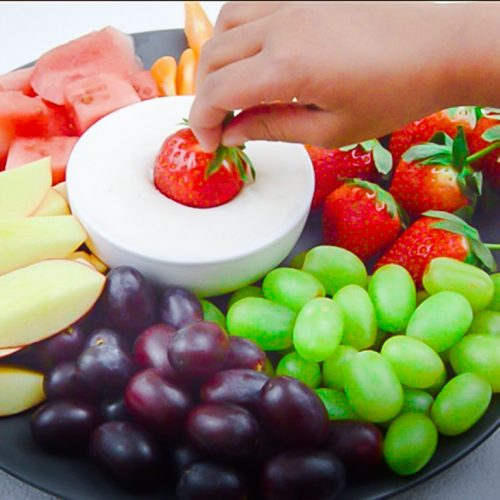a little hand dipping strawberry in a bowl of fruit yogurt dip placed in a fruit platter.