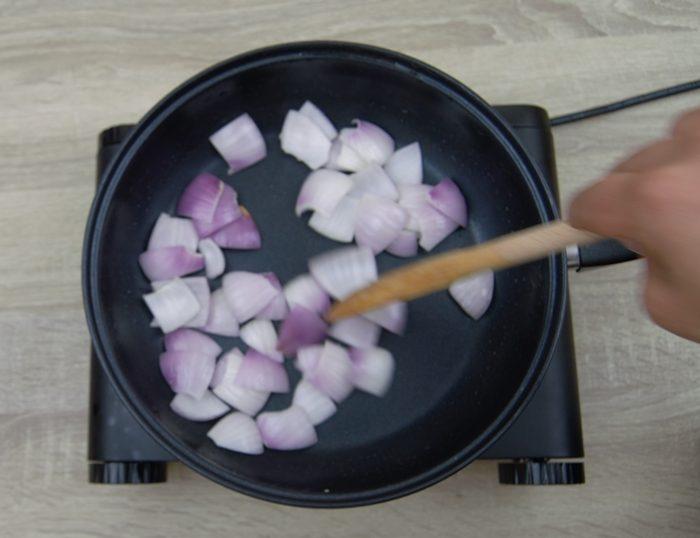frying onion cubes to make bhindi do pyaza