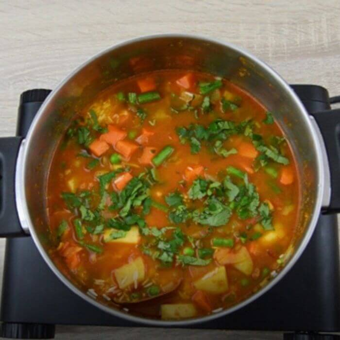 Final process of cooking vegetables with rice in eater and coriander.
