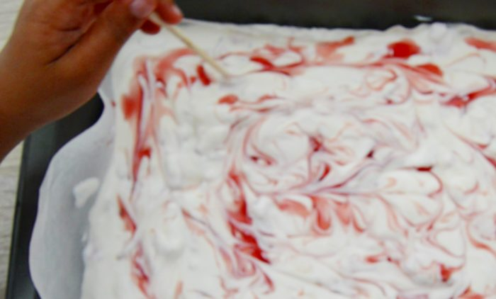 swirling strawberry sauce around yogurt with chopstick.