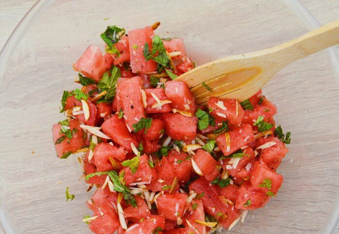 combining all ingredients to make watermelon salad.