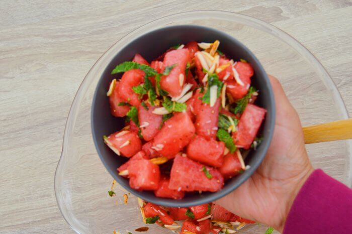 holding watermelon salad in a black bowl.