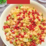 pin image with text overlay on top on red background showing a bowl of chana chaat on wooden background with small bowls of coriander and pomegranate.