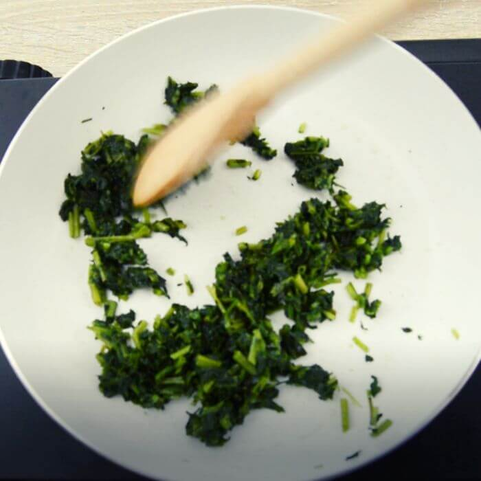 sauting methi in a white pan.