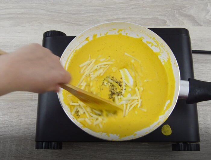cooking carrot sauce with cheese and mixed herbs.