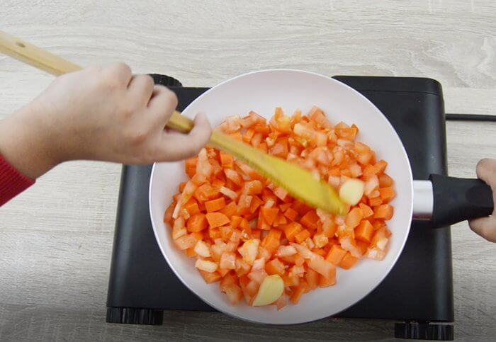 cooking tomatoes, carrots and garlic in a pan.