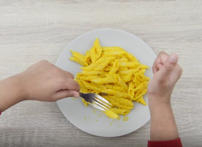 child taking a bite of carrot pasta with fork from a plate.