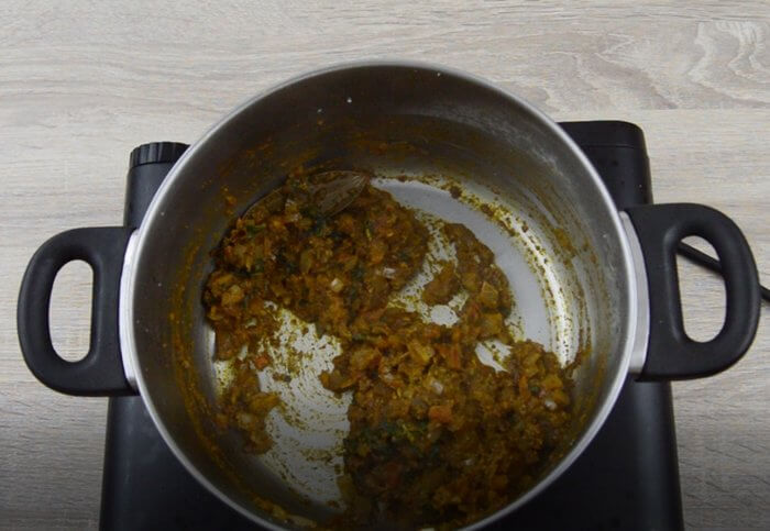 cooking tomatoes, ground paste and dry spices with onions.