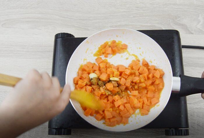 mixing dry spices to the vegetables.
