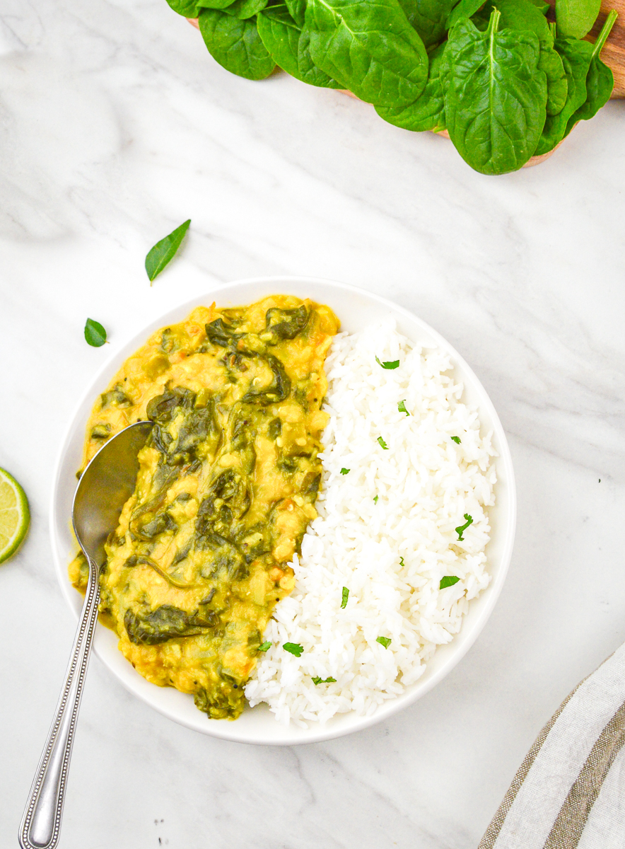dal palak with rice in a white bowl placed on white counter top.