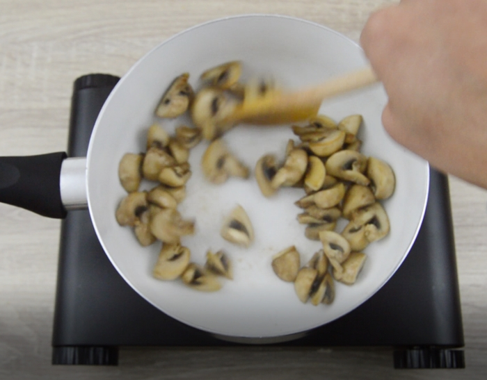 cooking mushrooms in a white pan.