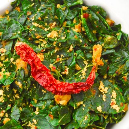 close up shot of moringa leaves curry in a white bowl with dry red chilli on top.