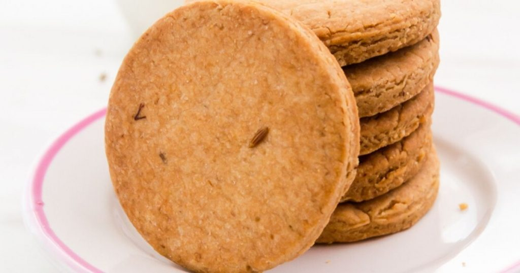 close up image of stack of jeera biscuits with one on the side in a white plate.