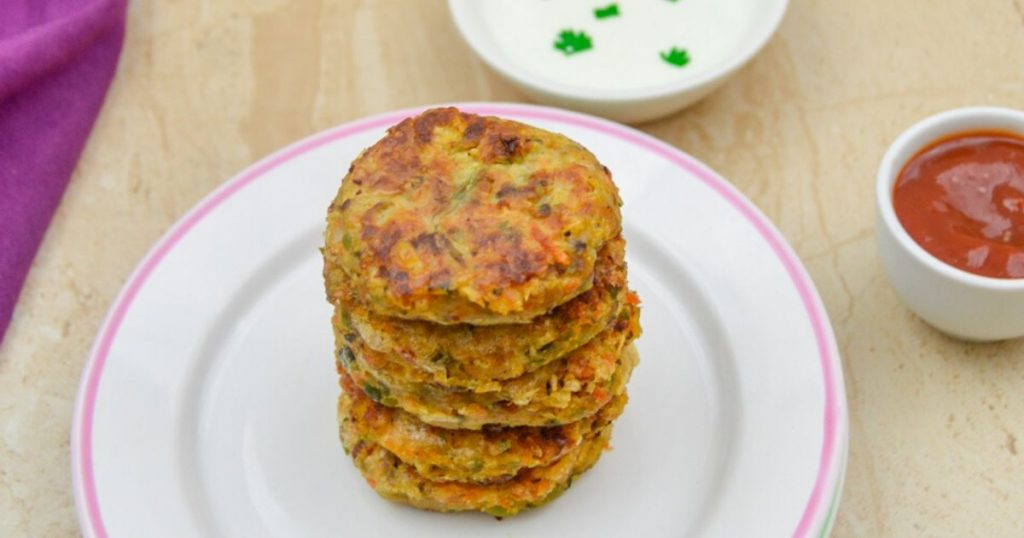 stack of chickpea patties on 2 side plates on a granite with a bowl of yogurt dip, tomato sauce and a purple cloth behind it.
