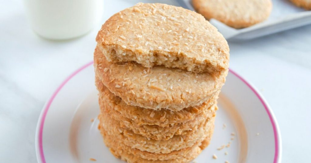 close up shot of stack of coconut biscuits in a white plate with a tray of them behind.
