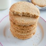 pin image of stack of coconut biscuits in a white plate with a tray of them behind with text overlay.