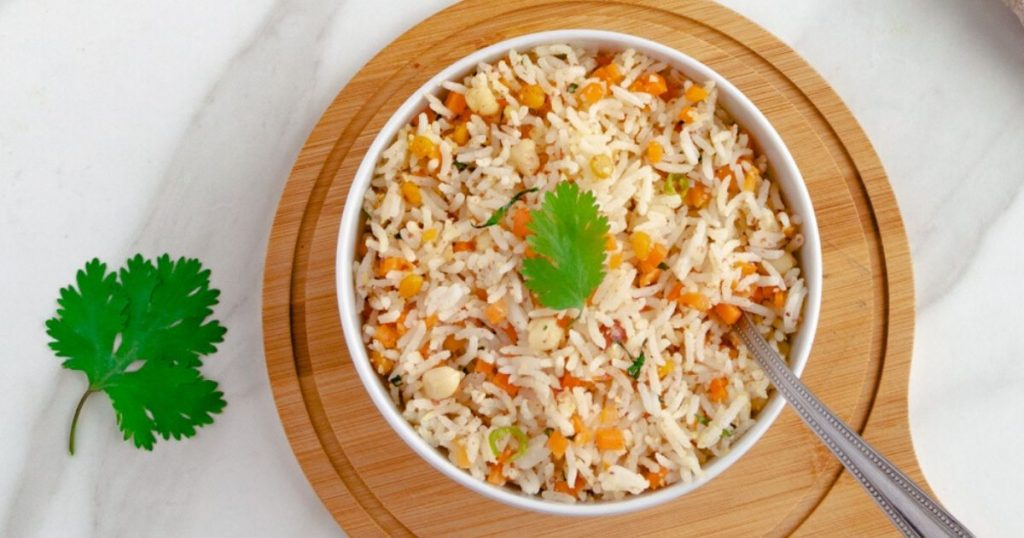 close up shot of carrot rice in white bowl with a spoon on wooden board.