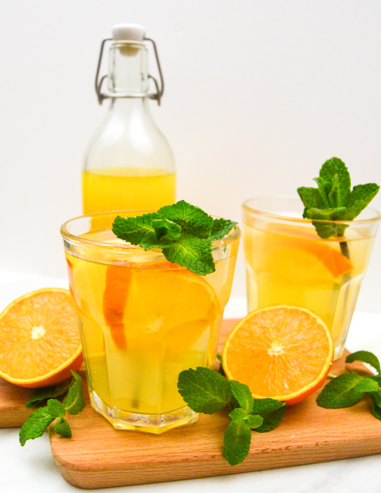 orange drink in 2 glasses with a bottle of orange syrup placed on wooden board.