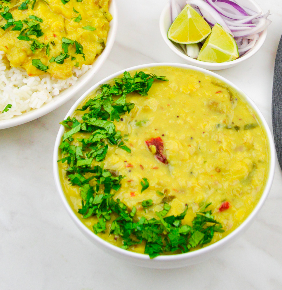 mango dal in a white bowl garnished with coriander.