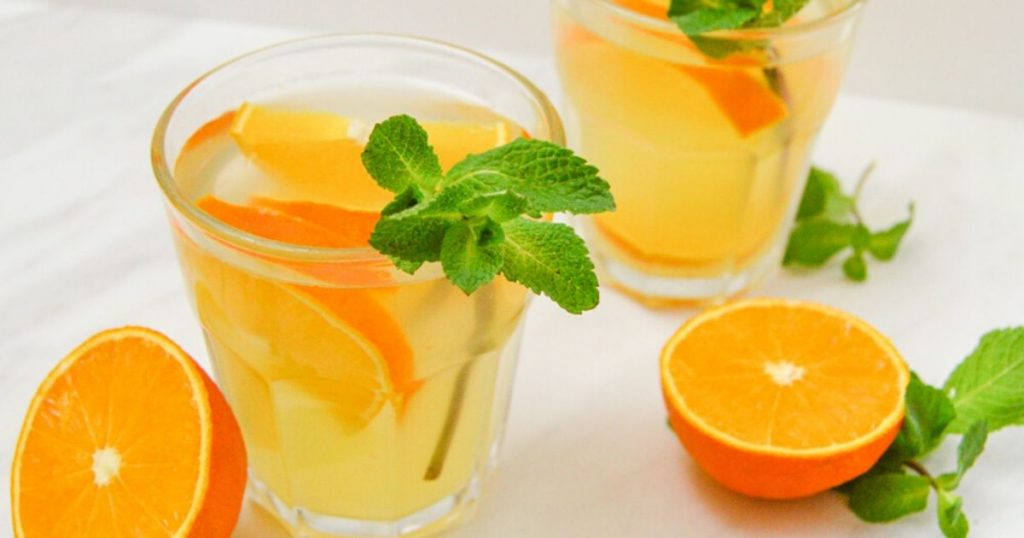 orange syrup in 2 glasses with mint sprig and half cut oranges on a marble.