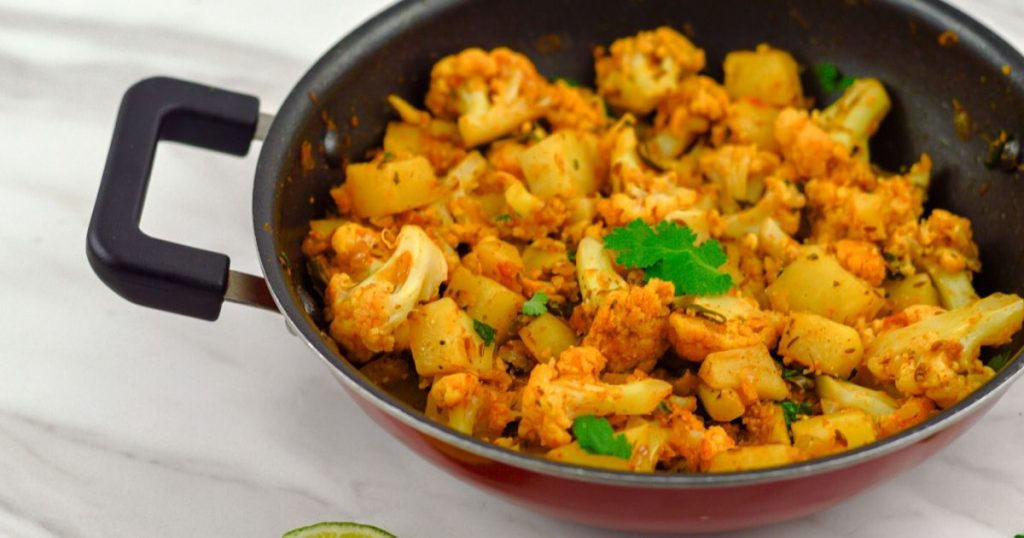 aloo gobi in a black pan placed on white table.