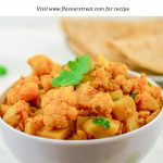 pin image of aloo gobi in white bowl with chapatis in a plate on marble background with text on white background at top.