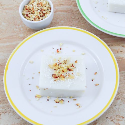 coconut pudding topped with chopped walnuts on plate placed on a table.