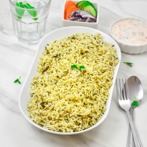 Pin Image of Methi Pulao in a white bowl on a marble background with cutlery, bowl of raita, salad and glass of water.