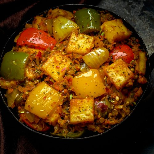 curry in black kadai with mixed peppers and paneer cubes on top placed on black pan with brown cloth on side.