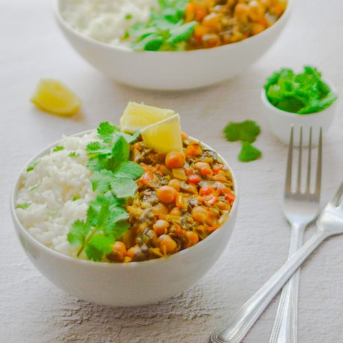 white bowl filled with white rice, chickpea and spinach curry with coriander and lemon wedge placed on white table along with 2 forks, pinch bowl of coriander and 2nd bowl of rice and curry behind.