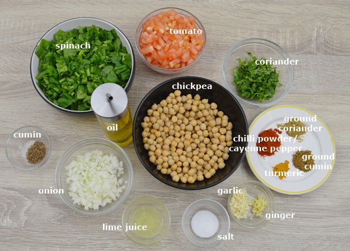 spices, oil, vegetables, chickpea in individual bowls placed on wooden table.