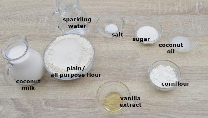 sugar, salt, flour, coconut milk, sparkling water, vanilla placed in an individual bowls on a table.
