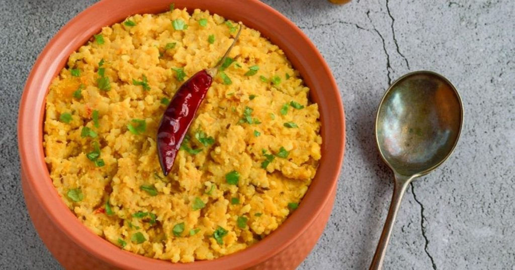 brown bowl filled with khichdi and topped with red chilli placed on a granite along with a serving spoon.