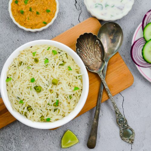 peas pulao in a white bowl and 2 spoons placed on a wooden chopping board along with a bowl of gravy, raita, sliced onion on a granite.