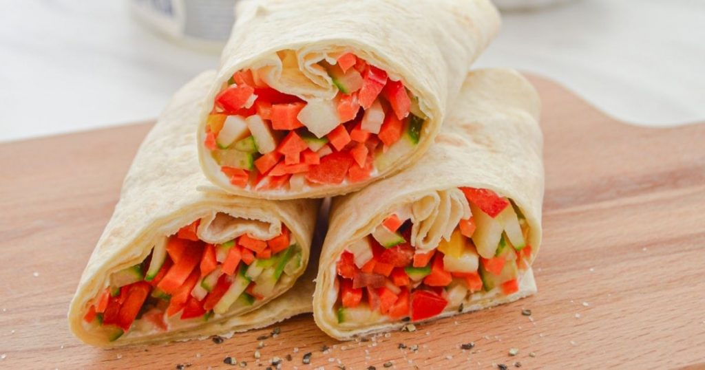 three cut tortilla wraps filled with vegetables placed on a wooden board with crushed pepper sprinkled on board.