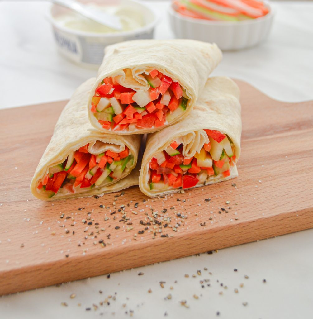 three veggie wraps placed on a wooden board with a cheese tub and a bowl of sliced vegetables behind it.