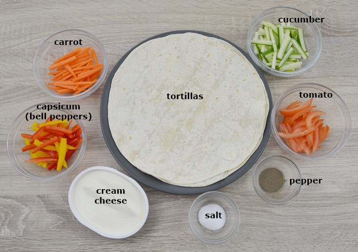 tortillas, slices vegetables, cheese and seasonings placed on a table.