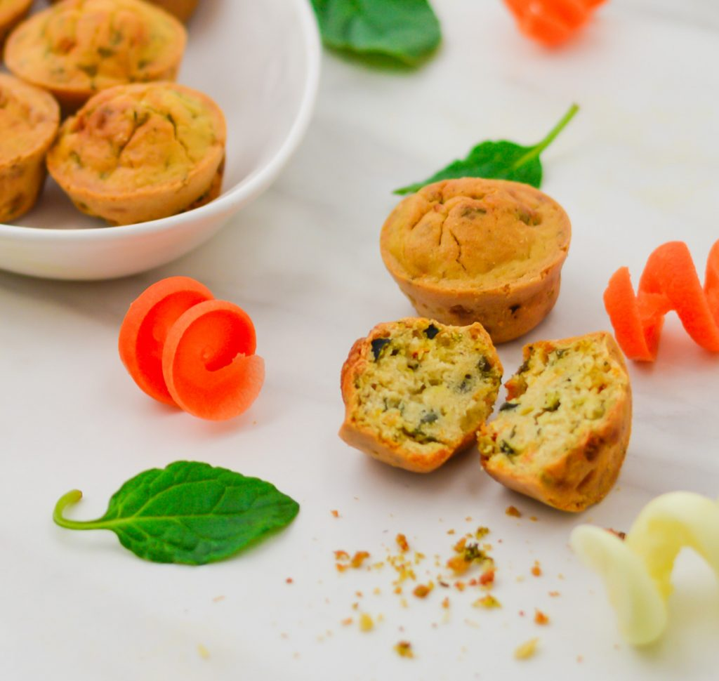 mini vegetable frittatas arranged in a plate and two on the marble with one cut into half and few vegetable curls and spinach leaves.