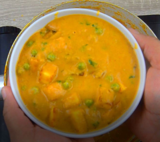Holding a white bowl of malai matar paneer in a hand.