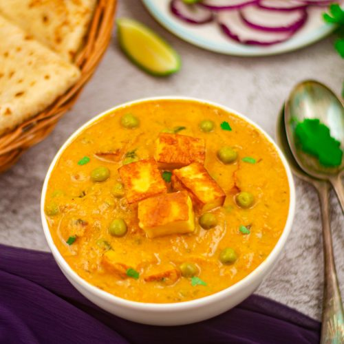 malai matar paneer curry in a white bowl placed on a granite along with a basket of chapatis, a plate of onion rings, bunch of coriander leaves, 2 spoons and a blue cloth.